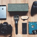 Camera, Phone, and other electronics laid out on table